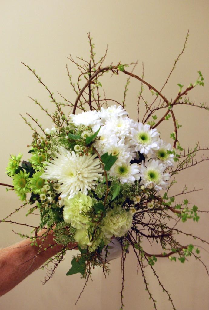 Bukett i vitt och grönt med svartvinbärskvistar